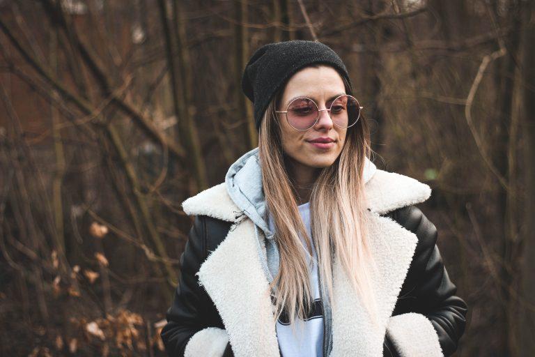 Imagem mostra uma moça usando uma jaqueta com gola de pelo, junto de um óculos escuro e um gorro.