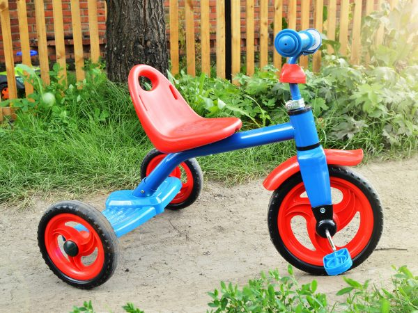 Colorful new tricycle children's bike outdoors on a Sunny summer day against the background of grass and road, the Concept of safety and protection of children on the street.