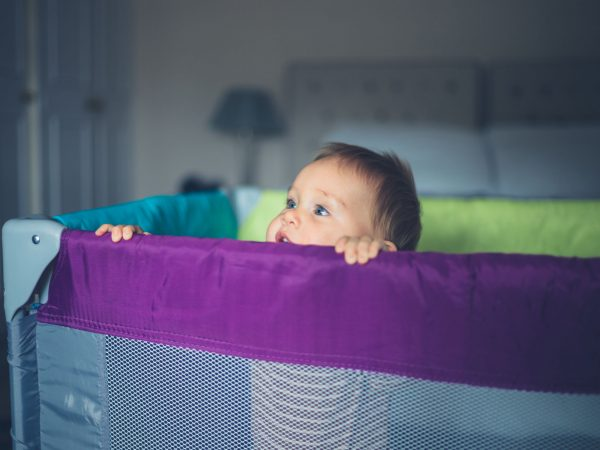 A happy little baby is standing in his playpen and is looking over the side