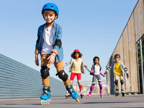 Portrait of schoolboy in helmet rollerblading with his friends at stadium outdoors